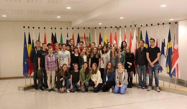 Foto der gesamten Gruppe vor den Flaggen der EU